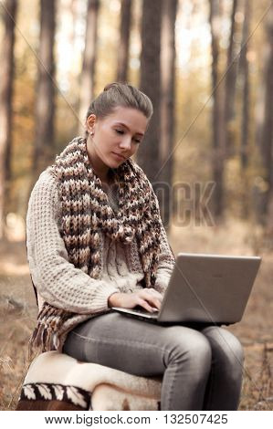 Hardworking, tired student work at the new project at laptop, computer in unusual atmosphere in forest outdoors. School girl do her homework at the computer and sit on the chair. Studens glances over.