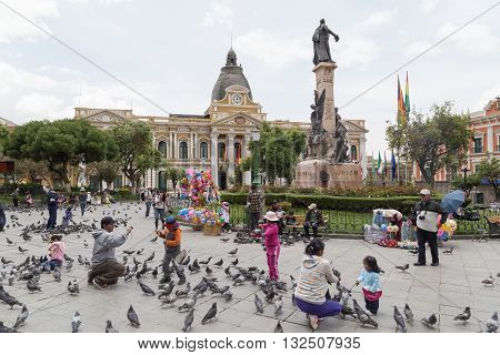 La Paz, Bolivia - October 24, 2015: People feeding pidgeon on Plaza Murillo.