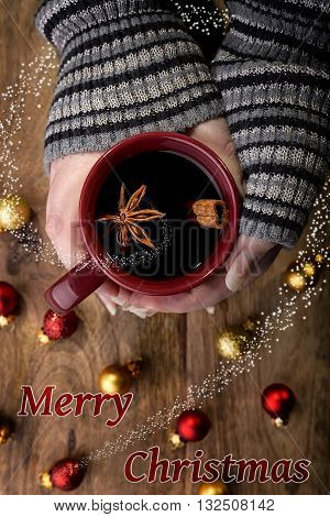 cup of mulled wine in female hands with cinnamon stick, star anise and red and gold christmas balls and merry christmas written and spiral snow