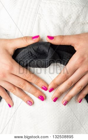 Hands with nail polish of a girl with a black belt in martial arts close up