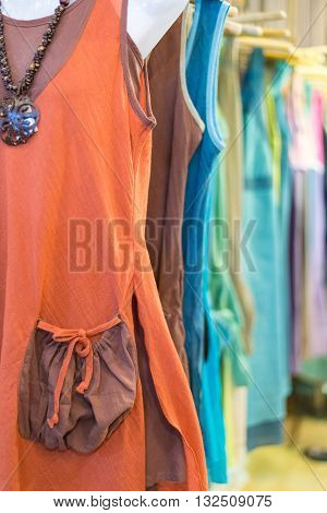 Female colorful cotton ethnic clothings in shop hanging on rack in boutique. Selective focus artificial light.