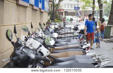 Hanoi, Vietnam - May 28, 2016: Close up of many motorcycles of many brands on a row at a parking area in Hanoi capital. Motorbike is the most popular vehicle for Vietnamese in Vietnam.