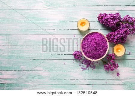 Spa set. Sea salt in bowl with candles and flowers on turquoise wooden background. Flat lay.Top view. Place for text. Selective focus.