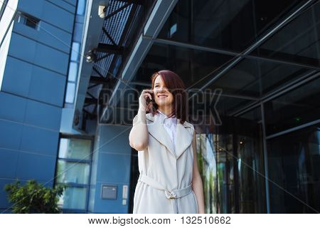 Young smiling businesswoman student professional outdoors talking on cell smart phone. Businesswoman smiling Life style