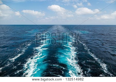 Wake of the cargo ship texture on the blue sea
