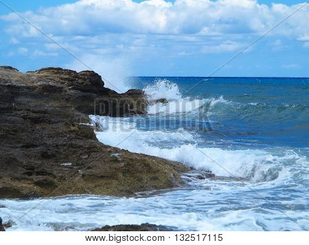 Big waves on rock coast blue sea and sky on Crete Greece