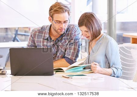 this business man and woman are very focused on their work, making sure the meet all their deadlines.