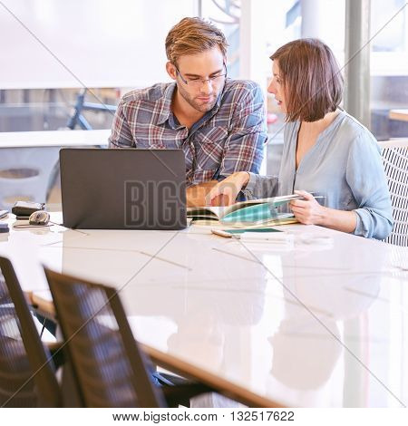 Mature female businesswoman reports her latest work to her male superior during their morning status report meeting together