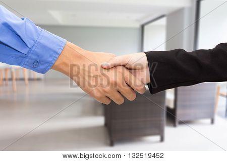Close up of businessmen shaking hands in room.