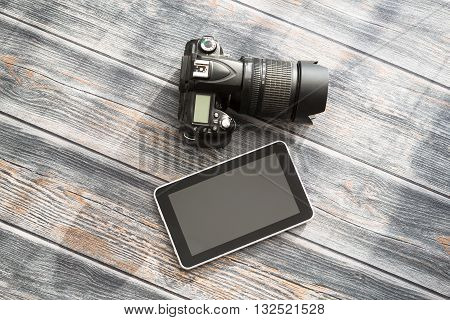 DSLR camera and tablet on a wooden table.