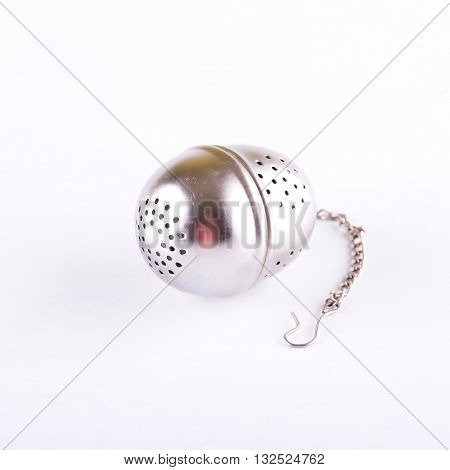 Square photo of teas strainer placed on white board. Tea strainer with small chain on white background with shadow. Strainer from silver metallic material. Strainer for preparing of tea.