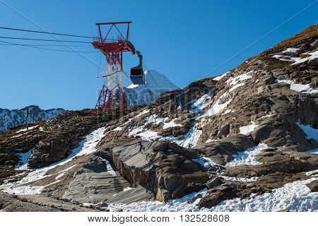 cabin lift on the aerial railway on background of snowy mountains and blue sky. Austrian Alps.