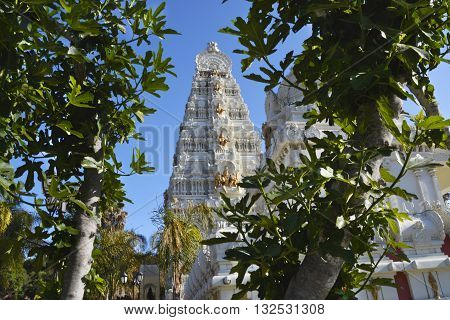 MALIBU, CA - JUNE 1 2016: Malibu Hindu Temple is shown standing tall through a clearing of trees.