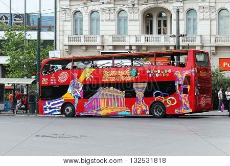 ATHENS GREECE - MAY 02; Red tourist sightseeing double decker bus on route in Athens Greece - May 02 2015: Famous hop on hop off sightseeing bus company with tourists riding around in Athens.