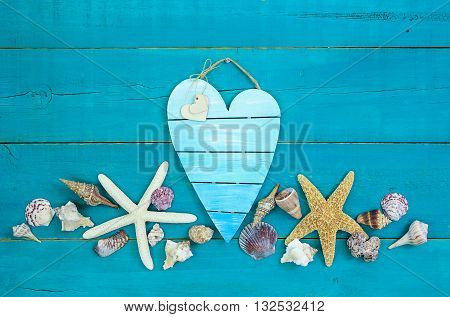 Seashells and starfish on antique rustic teal blue wood background; blank broken heart beach sign with hearts