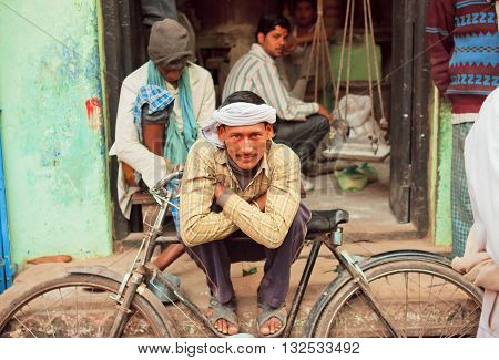 VARANASI, INDIA - JAN 1, 2013: Happy poor man sitting with his cycle on the street of poor area of indian city on January 1, 2013. Varanasi urban agglomeration had a population of 1435113