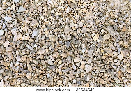 A close up background of rough textured tan colored crushed gravel screenings.