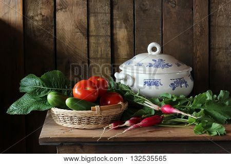 Vegetables in the basket. Still life with fresh vegetables and a tureen on the background of boards in rustic style.