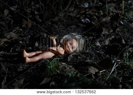 Scary doll lying at dark forest. Conceptual scene of child abuse. Crime scene.