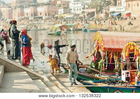 MADHYA PRADESH, INDIA - DEC 27, 2015: People crossing the river by riverboat of an old indian city with rustic indian houses and docks on December 27, 2015 in India. Population of Chitrakoot is 22294 people