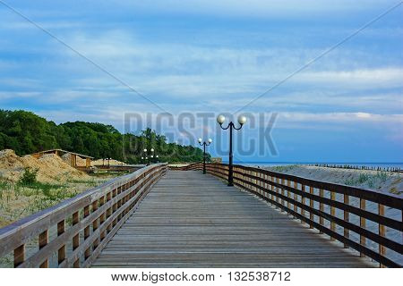 wooden promenade on the beach with lampposts and green forest background at sunset. perspective view