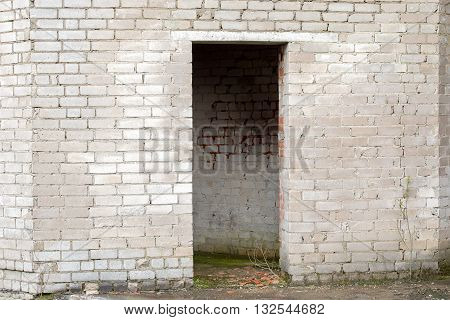 white cracked brick wall with a doorway of an abandoned house
