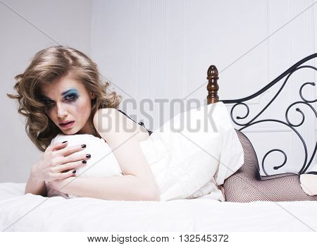 crying woman laying in bed depressed, real blond