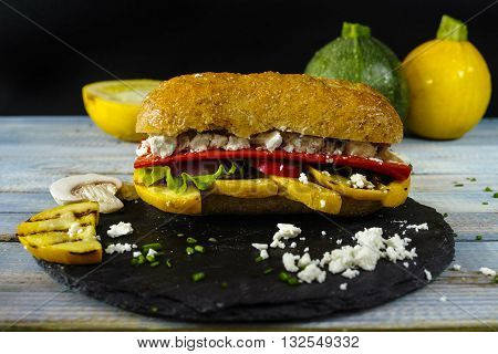 Healthy Vegetarian Veggie Sandwich with Grilled yellow squash zuccini Mushrooms Paprika Salad Feta cheese on blue table top
