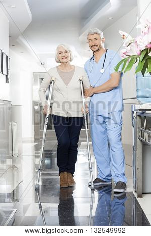 Male Physiotherapist Helping Senior Woman With Crutches