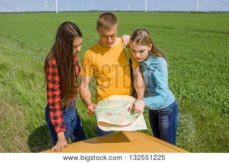 Three friends wanderer searching direction on location map on old car two girls and guy tourist searching road to hotel or direction seaon atlas in country road
