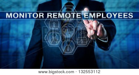 HR manager is pressing MONITOR REMOTE EMPLOYEES on an interactive virtual touch screen. Business metaphor and information technology concept for supervision of bring-your-own-device work practices.