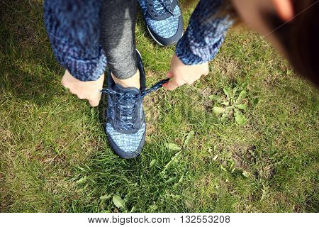 Woman tying up lace on sport shoes on green grass background