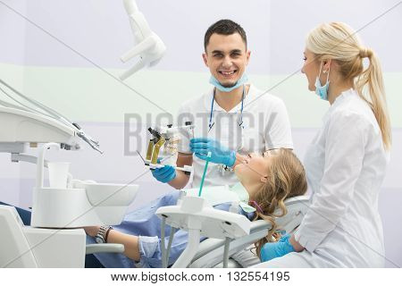 Pretty smiling girl in blue shirt and patient bib on the patient chair in the dental cabinet. Near her sits a smiling male dentist and a female assistant. They both wear white uniform with blue latex gloves and blue masks. Dentist also has binocular loupe