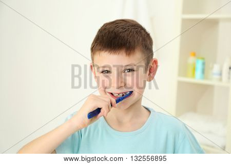 Smiling little boy brushing teeth, close up