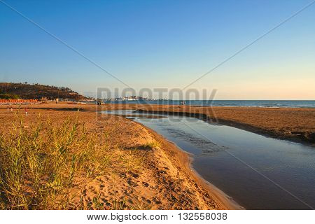 Summer seascape.Gargano coast: bay of Vieste.-(Apulia) ITALY-Portonuovo beach is a succession of fine sand dunes,crossed by many little kars streams,that cool the visitors in the hot summer time.