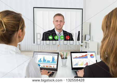 Two Businesswomen With Graphs On Laptop Videoconferencing In Office