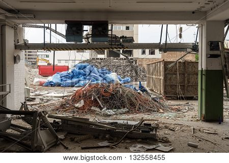 Demolition of large industrial buildings with piles of different parts and heavy machinery as seen through the ground floor of one of the buildings