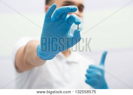 Dentist in a white uniform with blue latex gloves holds a dental implant in right hand. He shows like hand sign. Blurry background. Horizontal.