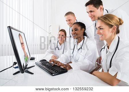 Group Of Doctors Videoconferencing On Computer In Hospital
