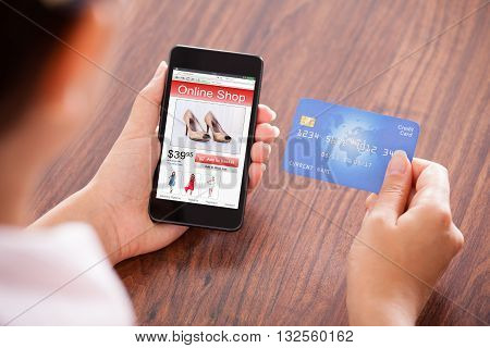Close-up Of Businessperson With Mobile Phone Showing Online Shopping Application And Credit Card