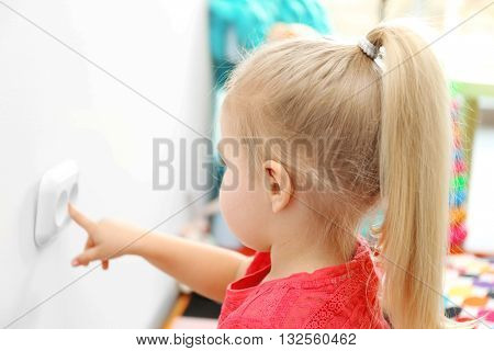 Little girl playing with power socket in the room