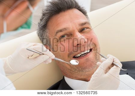Happy Mature Man Having Dental Check-up In Clinic
