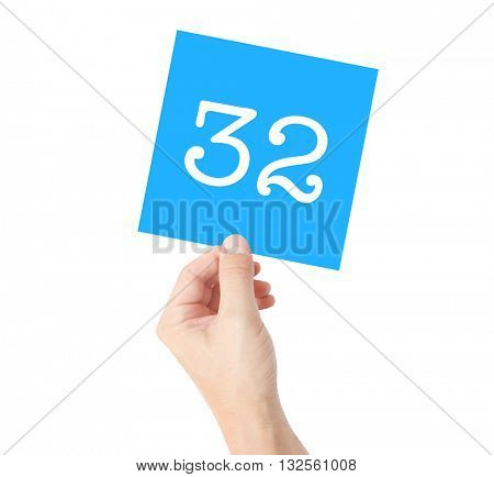 32 written on a card held by a hand