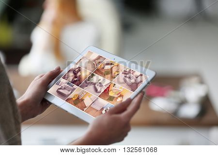 Woman monitoring cameras Live view on the tablets display. Home security system concept