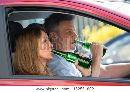 Mature Couple Drinking Alcohol While Sitting In Car