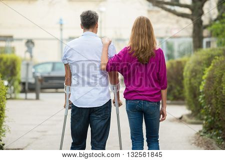 Rear View Of Woman With Her Disabled Husband Standing On Street