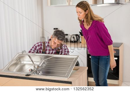 Woman Looking At Male Plumber Fixing Stainless Steel Sink