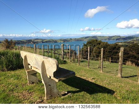 Wooden bench overlooking a rural vista on Waiheke Island, New Zealand.