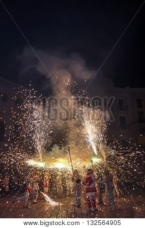 Traditional catalan spectacle called Correfocs (fire runs) or Ball de Diables (Devils' Dance). People dressed as devils and dancing with lighting fireworks fixed on devil's pitchforks. Reus Spain. Vertical.