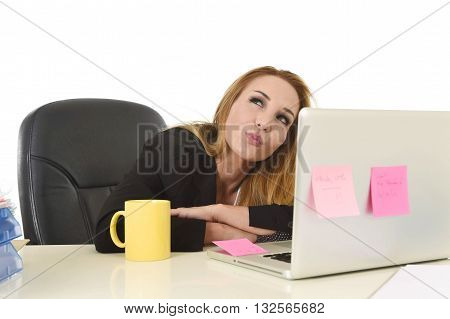 attractive 40s blond businesswoman working at office laptop computer sitting on the desk absent minded and thoughtful smiling happy as if thinking of vacation isolated on white background